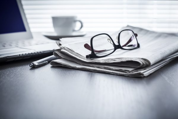 Newspaper with glasses and computer on table